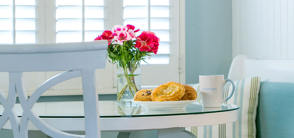 Glass top dining Table with pastries, coffee and pink flowers at Scripps Inn