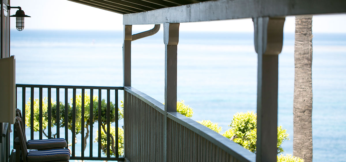 Deck view featuring a variety of trees and blue of the ocean from Scripps Inn in La Jolla Cove