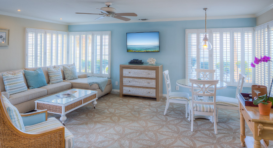 Vista Suites baby blue room with beige décor and tv on the wall with large windows