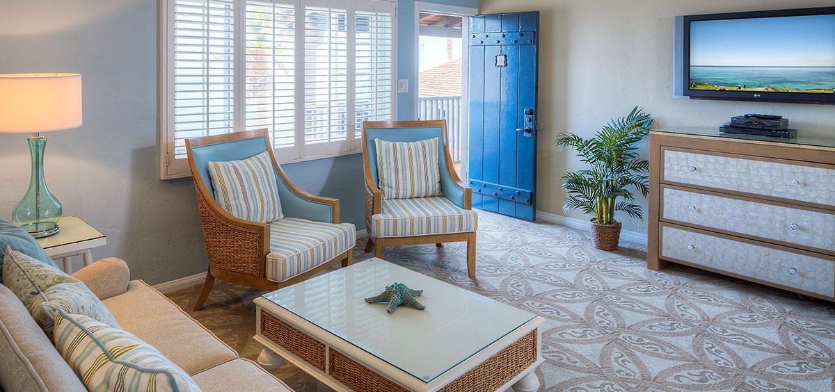 Light blue décor with white coffee table and light color chairs and couch with tv at Scripps Inn