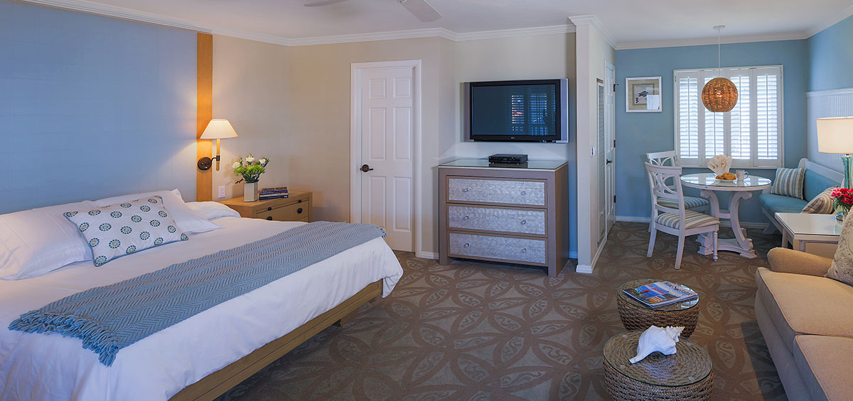 King Bed with small living area and dining area by window with light blue décor at Scripps Inn