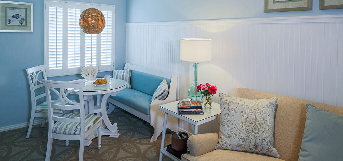 Scripps Inn small living space in la Jolla with light blue and white décor with small table & couch