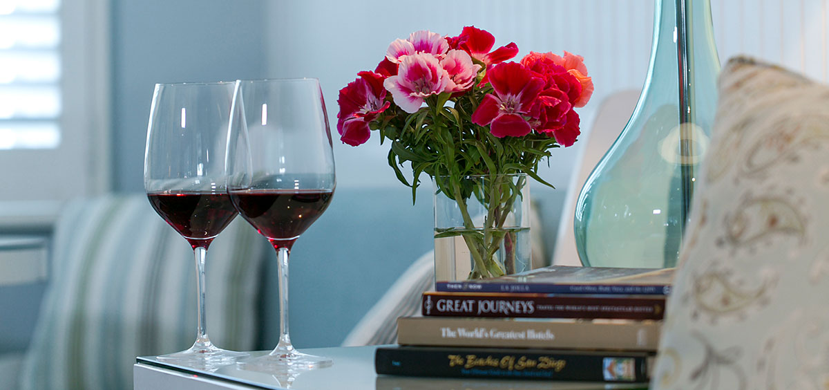 Two glasses of red wine on the side table with books, flowers and lamp at Scripps Inn