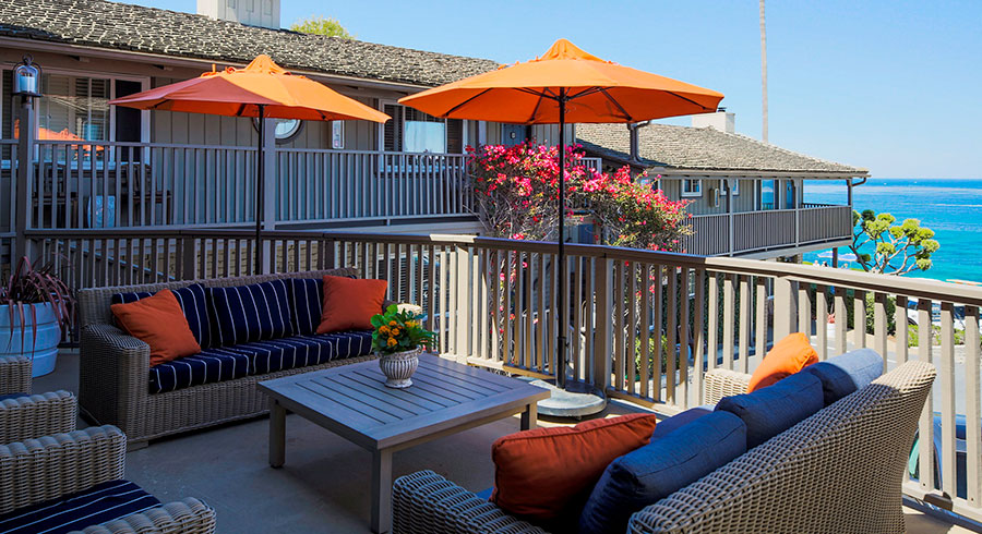 Orange and Blue with white stripped wicker chairs & Couches outside on deck of Scripps Inn