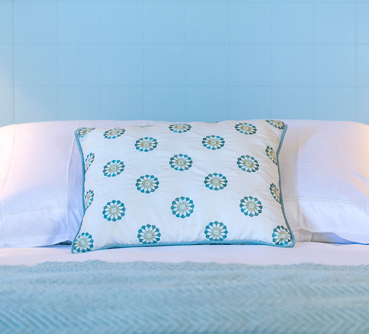 Light blue backboard over bed with pillows with flower pillow case at Scripps Inn